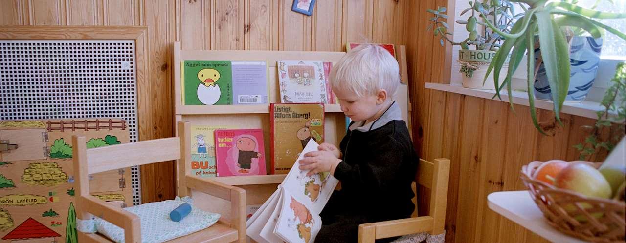 Fotografi på pojke som bläddrar i en bilderbok.